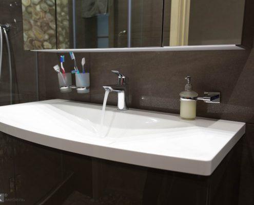 Белая раковина в коричневой ванной комнате